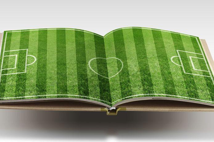 Ein aufgeschlagenes Buch. Darin abgedruckt ein Fussballfeld. Es verdeutlicht die theoretsiche Lehrarbeit der Schiedsrichtervereiningung Augsburg.