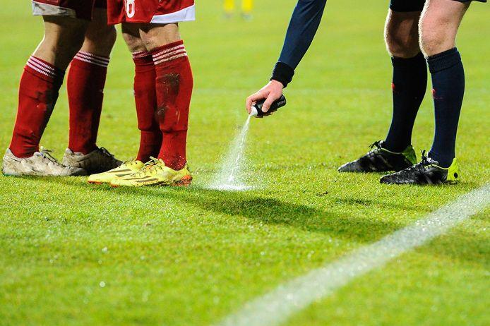 Ein Schiedsrichter sprüht mit einem Freistoßspray den Mauerabstand auf einem Fussballfeld