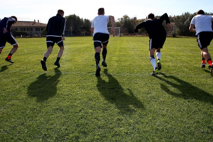 Spieler laufen auf einen Fußballplatz.