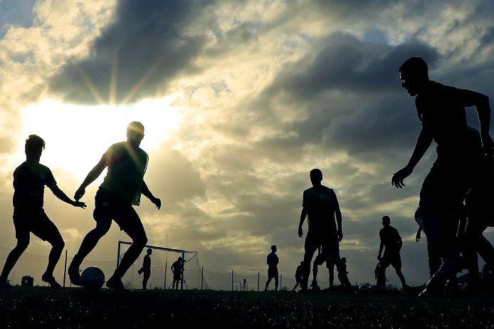 Fußballtraining bei wolkenbehangenem Himmel und Sonnenschein.